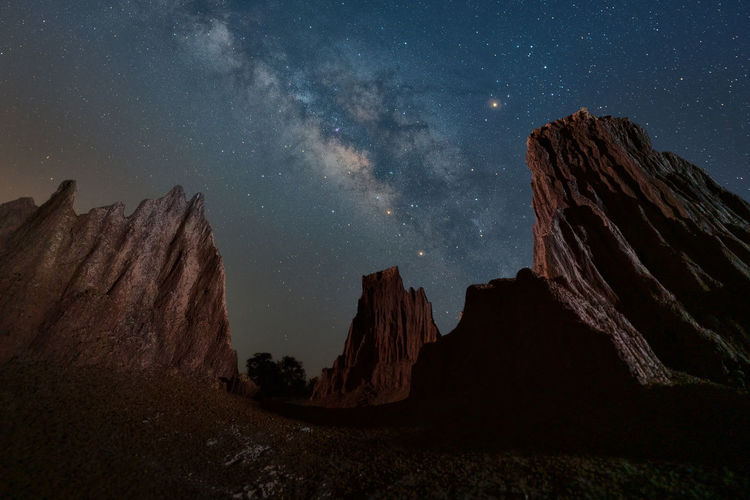 Panoramic view of rocks against sky at night