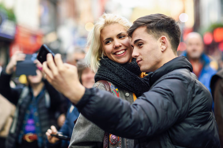 Happy couple of tourists taking selfie in a crowded street of London Photography Themes Two People Emotion Camera Adult Happiness Photographing Togetherness Smiling Women Smart Phone Couple - Relationship Young Adult Young Women Lifestyles Technology Men Portrait Selfie Real People Wireless Technology Positive Emotion Warm Clothing Outdoors
