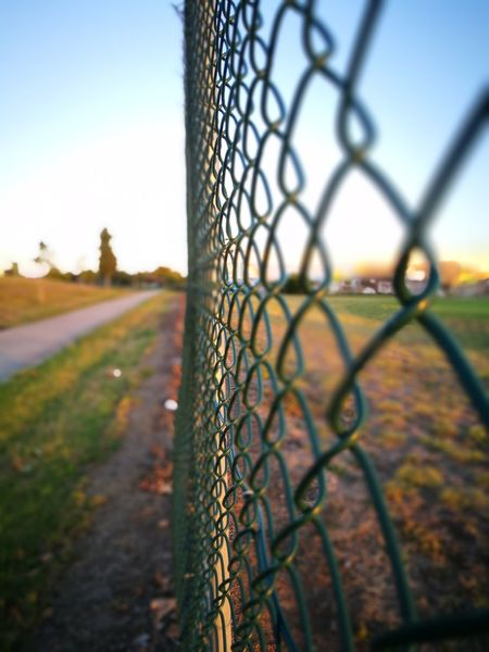 Fence Chainlink Fence Protection Security Metal Safety Outdoors Barbed Wire Grass Playing Field Selective Focus Sky Day No People Nature Security System Close-up