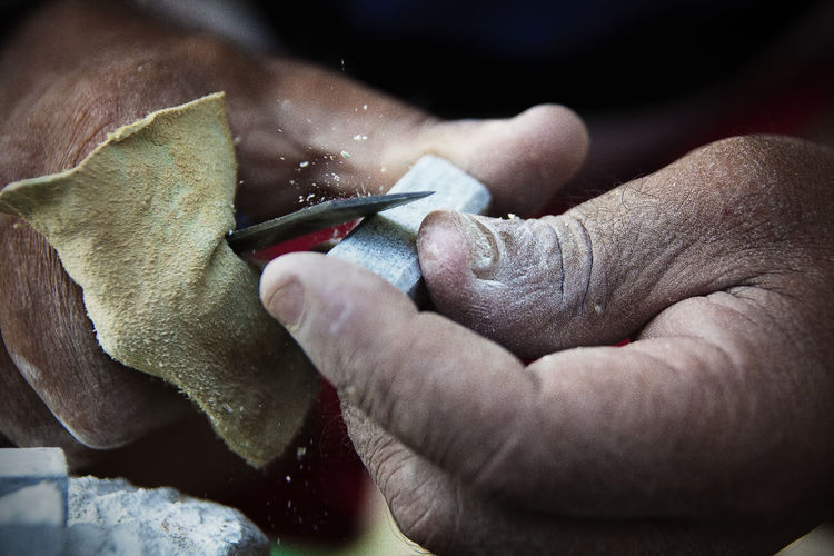 Close-up of hands carving stone