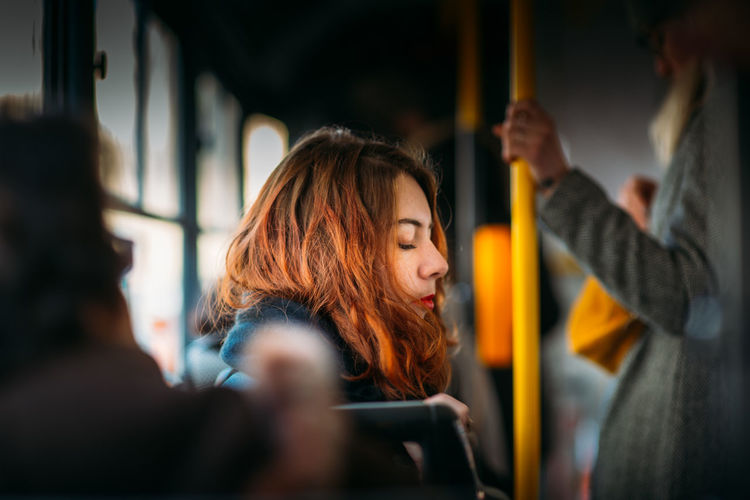 Portrait of young woman using mobile phone in bus
