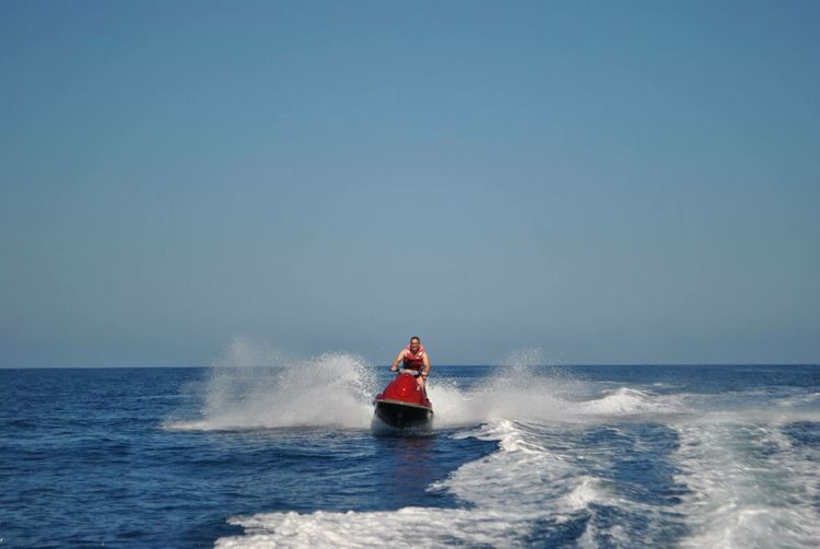 Man Jet Boating On Sea Against Clear Blue Sky