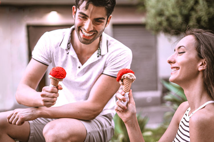 Young couple eating ice cream while sitting outdoors