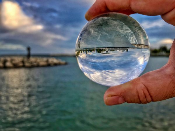Blurred Background Refraction Photography Glass Ball Lens Ball Focus On Foreground Lake Human Hand Water Crystal Ball Holding Reflection Outdoors Horizon Over Water Close-up