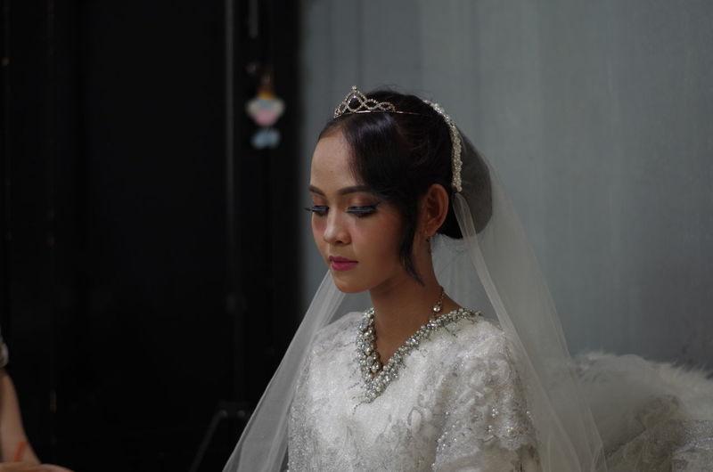 Bride sitting against wall