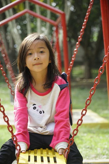 Portrait of girl sitting on swing in playground