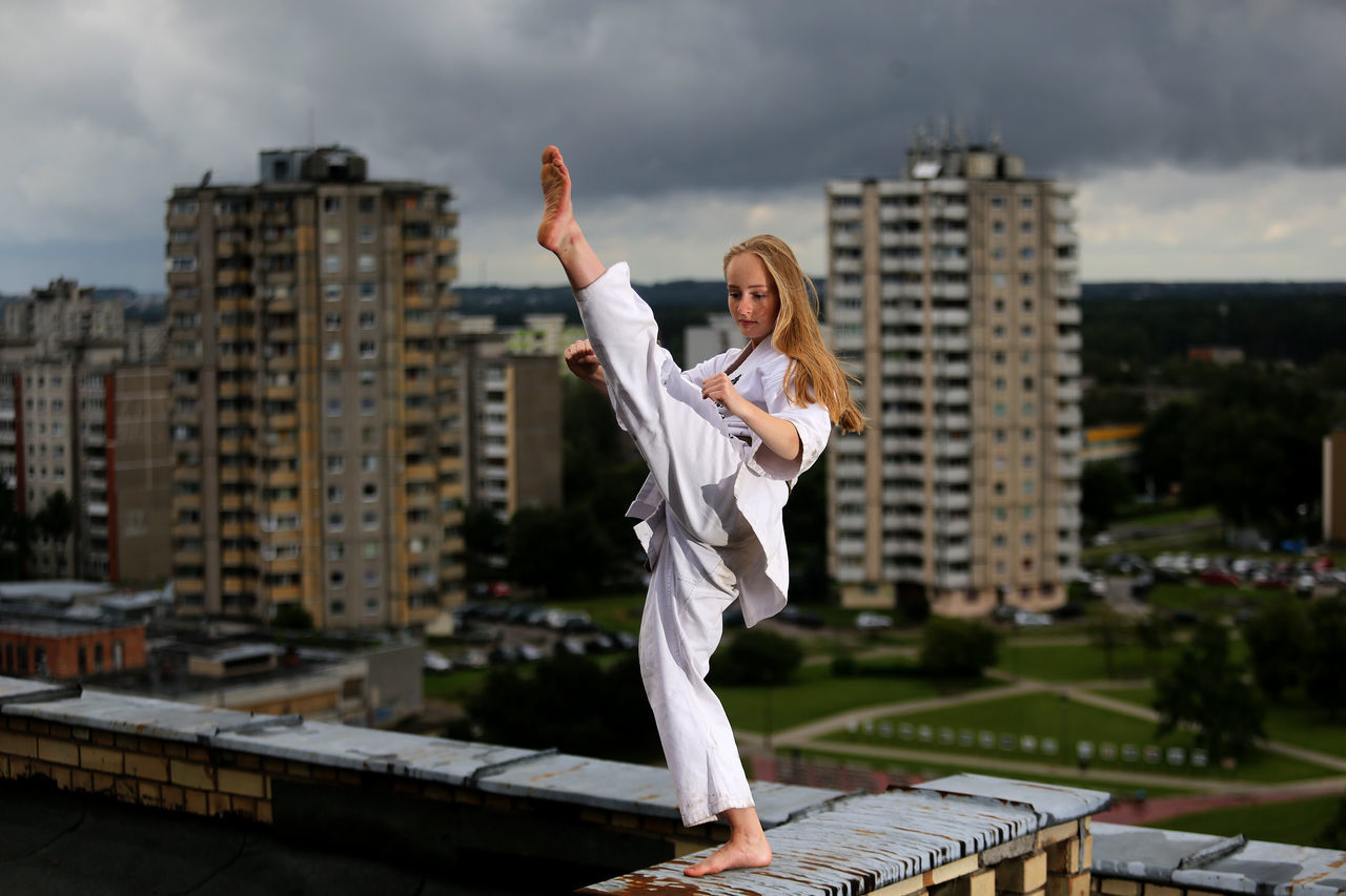 Woman practicing martial arts on retaining wall of building terrace