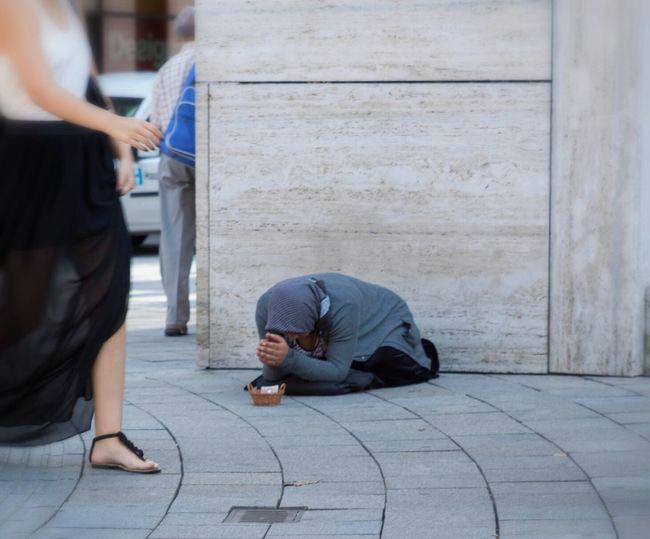 Woman walking by beggar on sidewalk