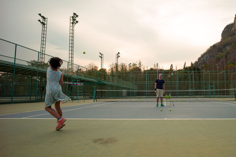 Portrait Asian girl plays tennis with her father and coach at outdoor court with stone mountain and forest background Real People Full Length Sky Child Sport Lifestyles Childhood Playing Women Leisure Activity Girls Females Rear View Nature People Men Sunset Two People Casual Clothing Outdoors Family Coach Train Court Tennis Practice Landscape Active Fun Healthy Eating Happy
