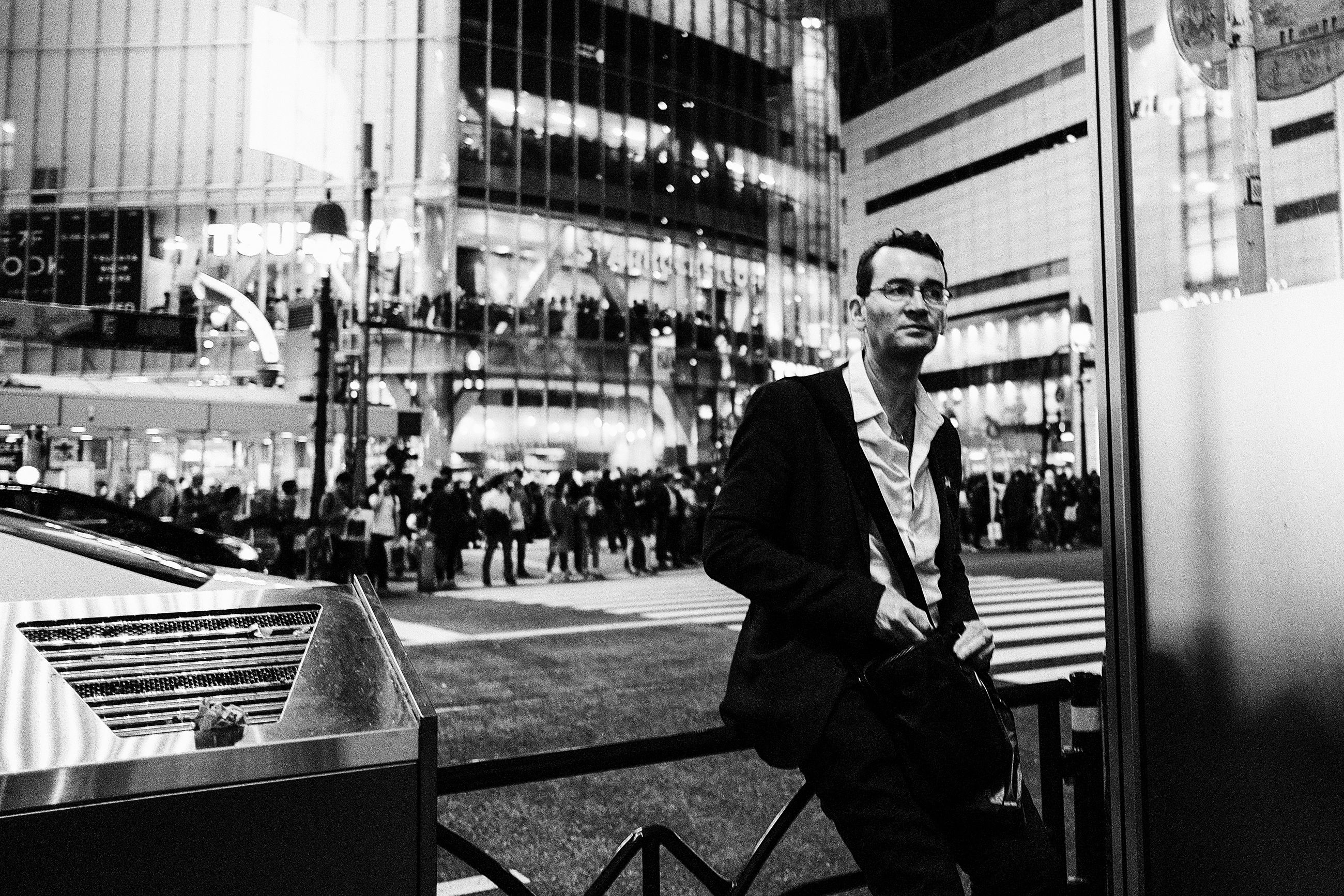 architecture, city, real people, one person, built structure, city life, building exterior, men, incidental people, leisure activity, lifestyles, street, young men, focus on foreground, three quarter length, young adult, standing, transportation, well-dressed, outdoors