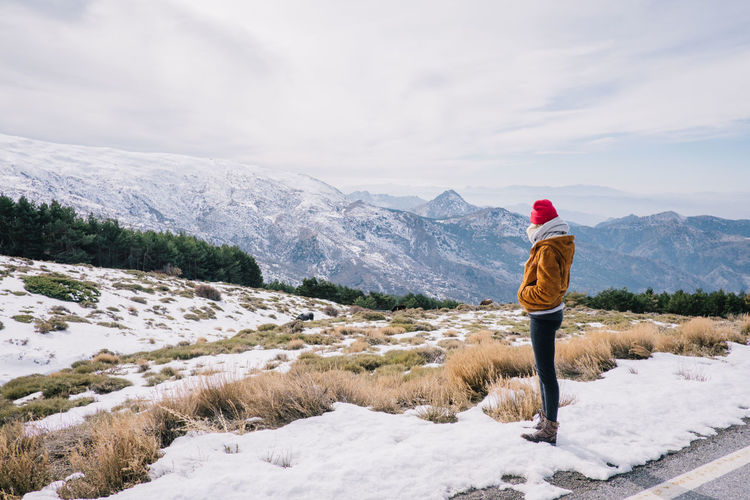 Side view of woman standing on snow while looking at mountains
