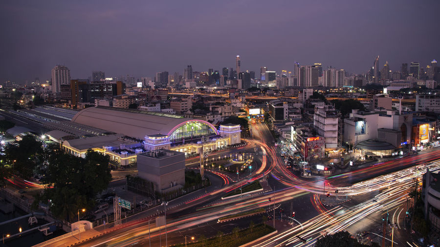 Hua Lamphong train station in sunset time , Bangkok , Thailand . Hua Lamphong Railway Station, Bangkok, Thailand Cityscape High Angle View Highway Transportation Long Exposure City Life Light Trail Architecture Building Exterior City Built Structure Illuminated Night Road Sky Motion Building Nature Street Speed Office Building Exterior No People Skyscraper Modern