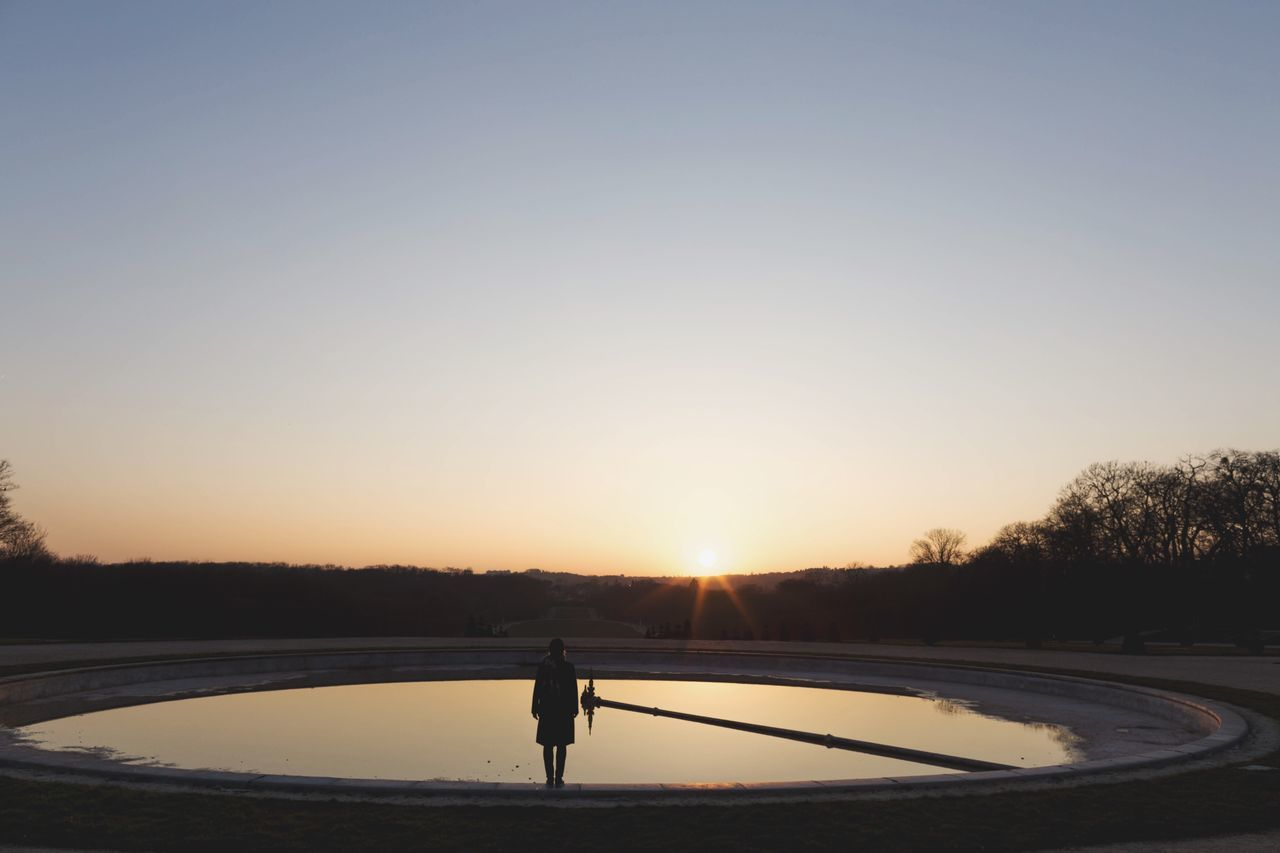 Rear view of woman standing by pond against clear sky during sunset