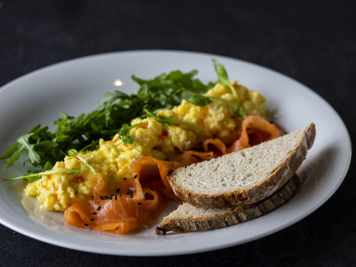 Scramble with salmon and arugula Scramble Scrambled Eggs Salmon Arugula Fish Food Food And Drink Freshness Healthy Eating Ready-to-eat Wellbeing Plate Vegetable Indoors  Close-up No People Meal Studio Shot Serving Size Still Life Garnish Bread Black Background Vegetarian Food Indulgence Meat Selective Focus Breakfast Temptation Snack