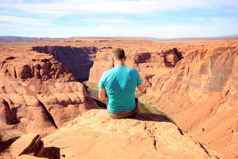 Rear view of man sitting on horseshoe bend edge