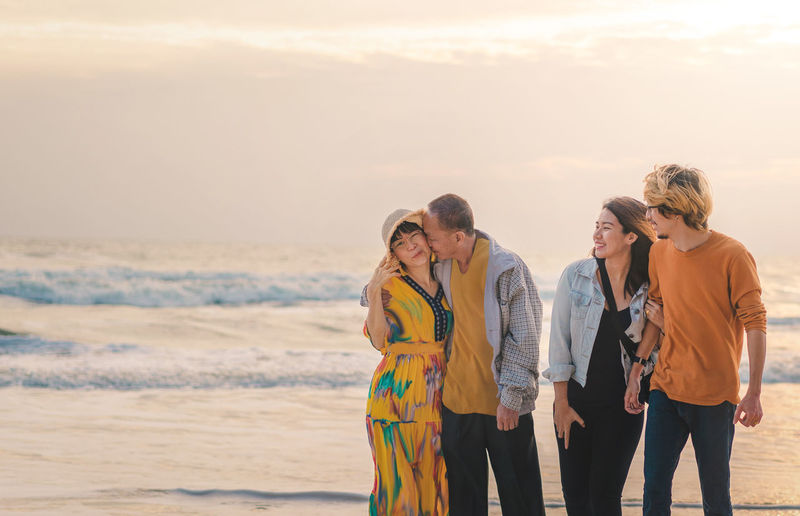 Cheerful family standing on beach during sunset