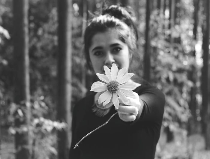 Portrait of young woman holding flower while standing in forest