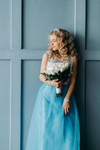 Midsection of woman wearing blue dress holding bouquet
