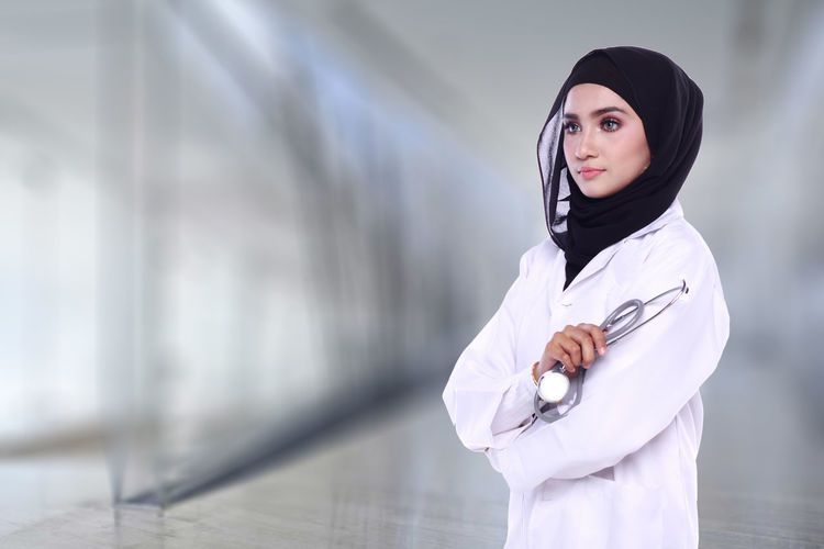 Female Doctor Standing Against Wall