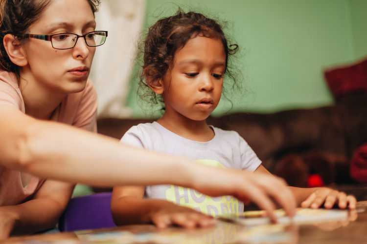 Mother assisting daughter in studies at home