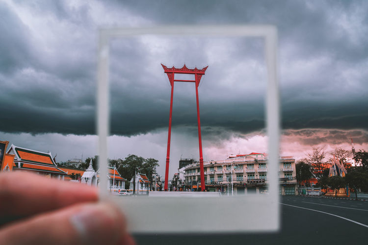 Cropped hand of person framing building in polaroid picture