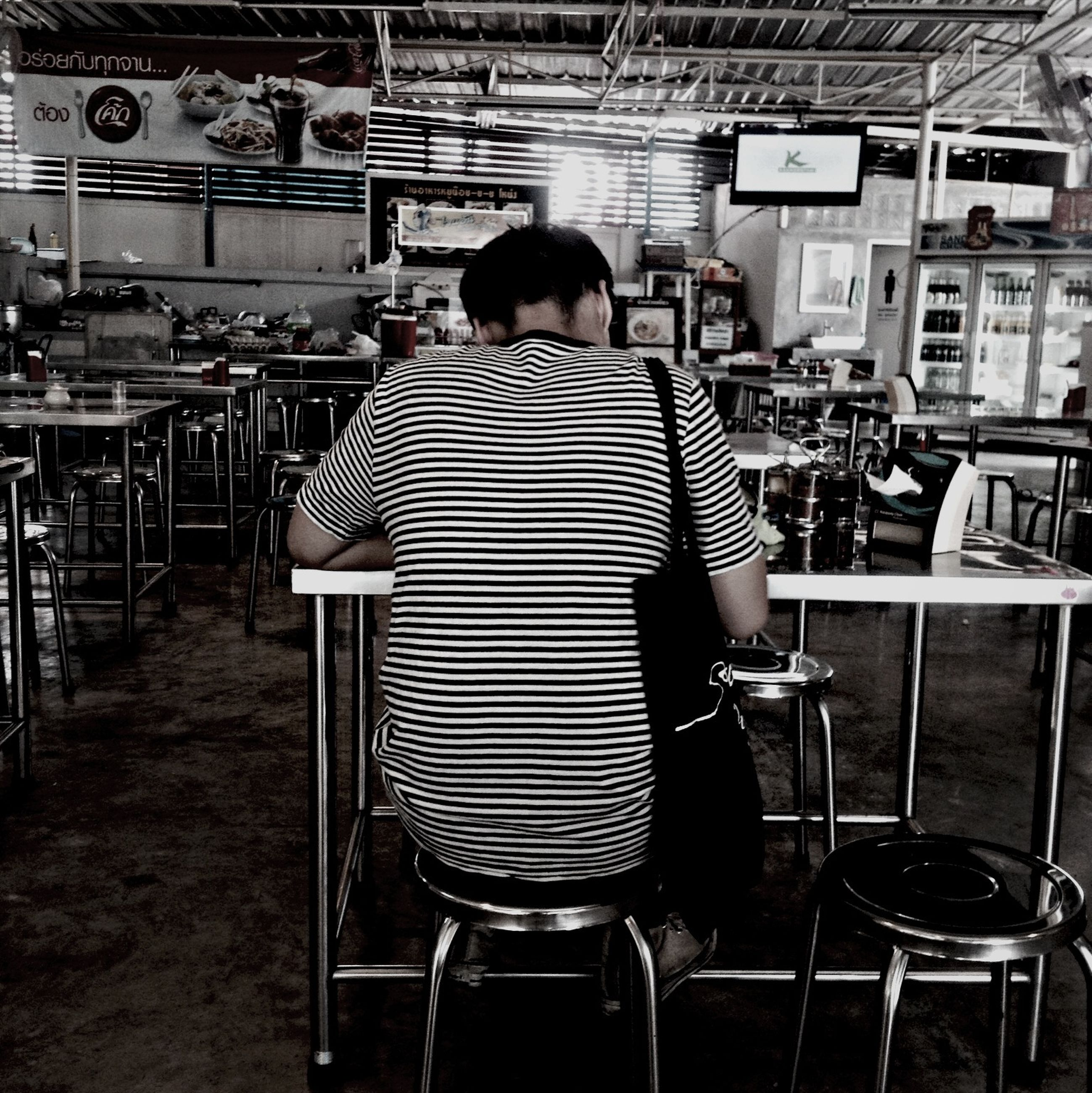 chair, rear view, men, sitting, lifestyles, indoors, full length, leisure activity, person, casual clothing, architecture, built structure, relaxation, seat, table, standing, sidewalk cafe
