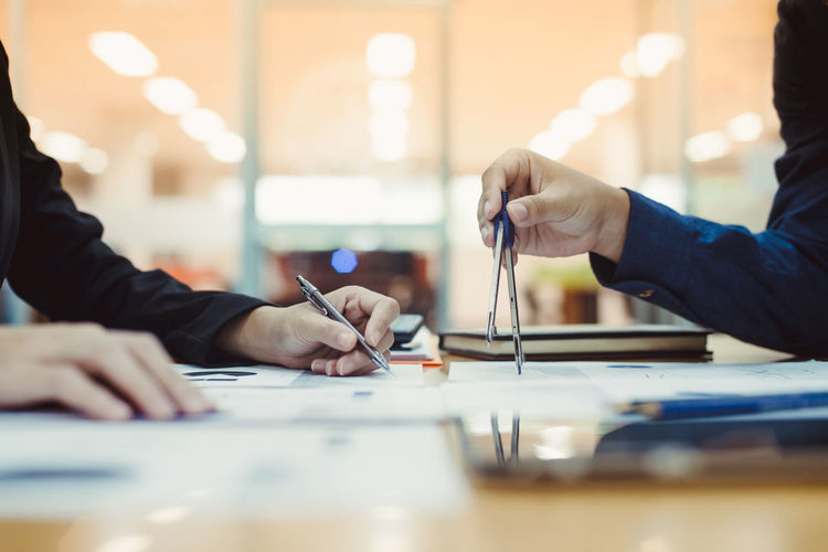 Midsection of businessmen working on table at office