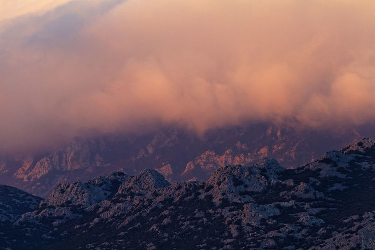 Scenic view of clouds above velebit  mountains against sky during sunset