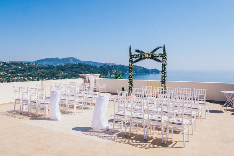 Empty chairs and tables by sea against clear sky