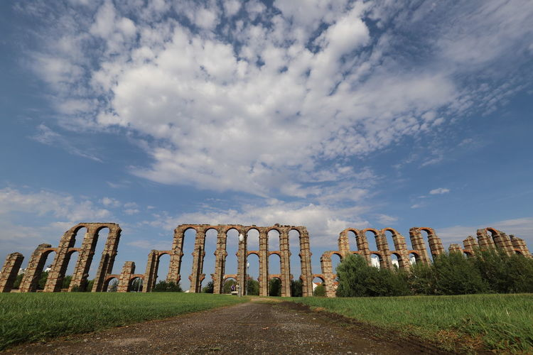 Wide angle of old ruin, roman aqueduct on field against blue sky with white clouds