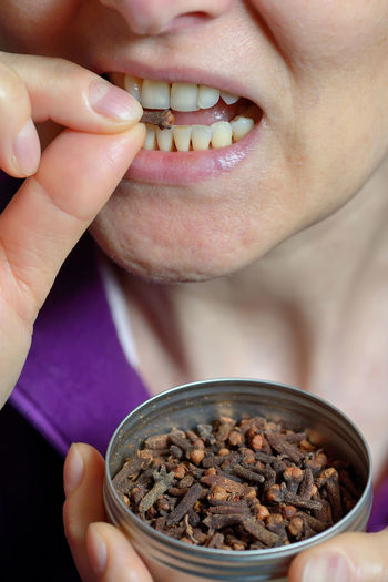 Woman chew dried clove spice for fresh breath Adult Adults Only Close-up Day Dried; Spice; Clove; Closeup; Herb; Healthy; Natural; Seed; Seeds; Brown; Food; Cuisine; Ingredient; Spicy; Aromatic; Condiment; Aroma; Dry; Scent; Scented; Flavor; Flavouring; Cloves; Girl; Mouth; Eating; Eat; Woman; Chewing; Open Mouth; Female; Young; P Eating Healthy Eating Human Body Part Human Lips One Man Only One Person Only Men People Smiling