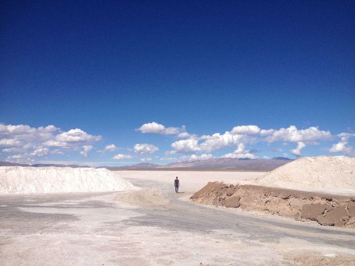 Man walking on landscape against blue sky