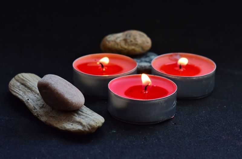 Close-up of lit tea light candles and stones on table