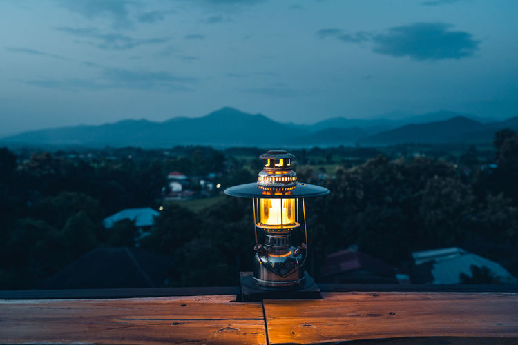 View of lantern on table against mountain