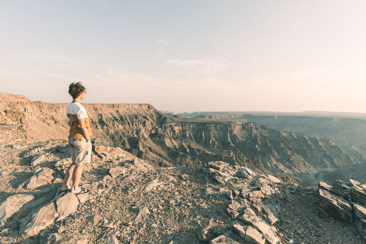 One person looking at the Fish River Canyon, scenic travel destination in Southern Namibia. Expansive view at sunset. Wanderlust traveling people. Keywords: fish river canyon,one person,looking at view,river,canyon,real people,expansive,people traveling,summer,namibia,travel destinations,valley,Landscape,cliff,sightseeing,vacation,desert,top,adventure,female,travel,mountains,exploration,summit,scenic,tourism,outdoors,panorama,landmark,majestic,above,famous,scenics,panoramic,wide-angle,clear sky,sunlight,viewpoint,idyllic,national park,horizon,remote,tourist,highland,relaxation,africa,happiness,extreme terrain Fish River Canyon