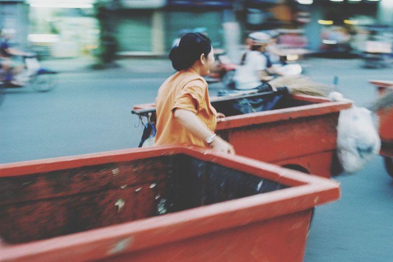 Woman Pulling Large Garbage Bin On Street In City