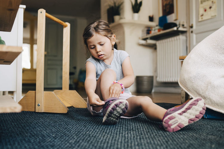 Cute girl sitting on floor at home
