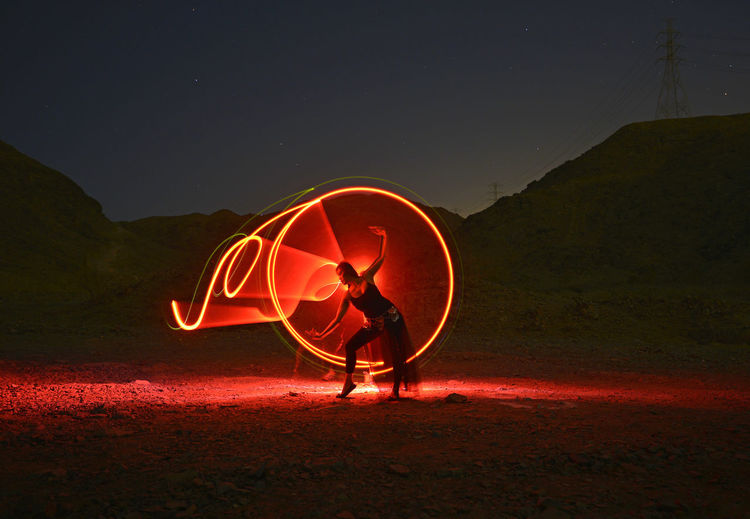 Midsection of man with illuminated light painting against sky at night