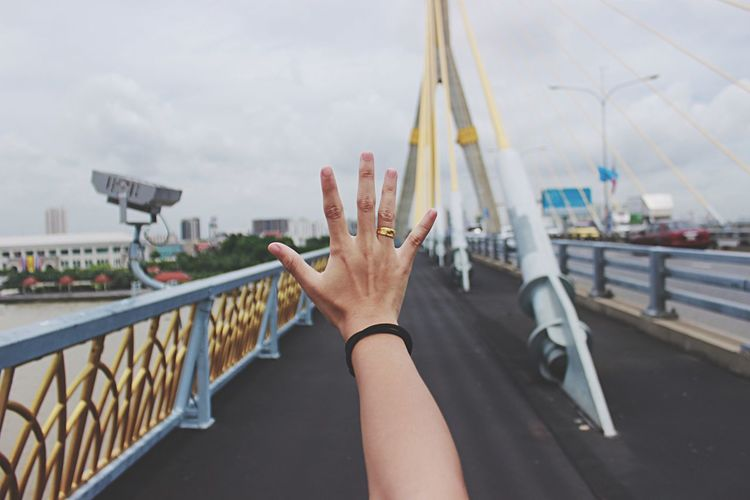 Cropped hand of woman on bridge against sky in city