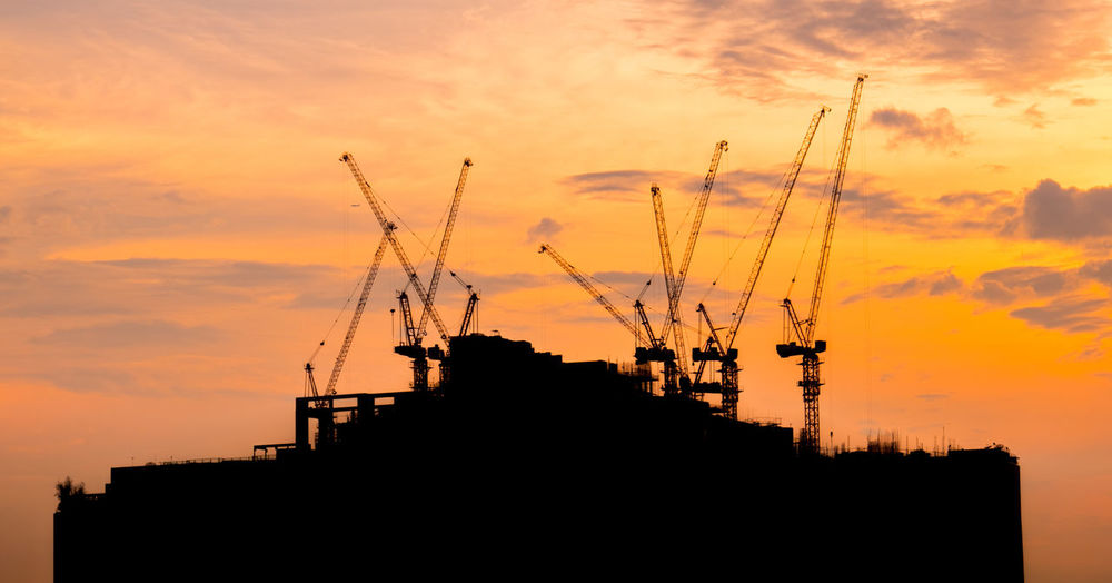 Low angle view of silhouette cranes against buildings during sunset