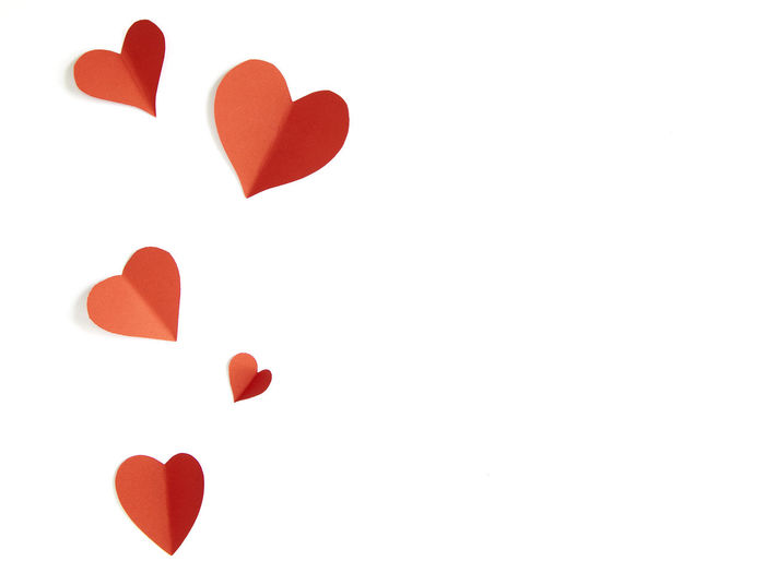 High Angle View Of Heart Shape Papers Over White Background