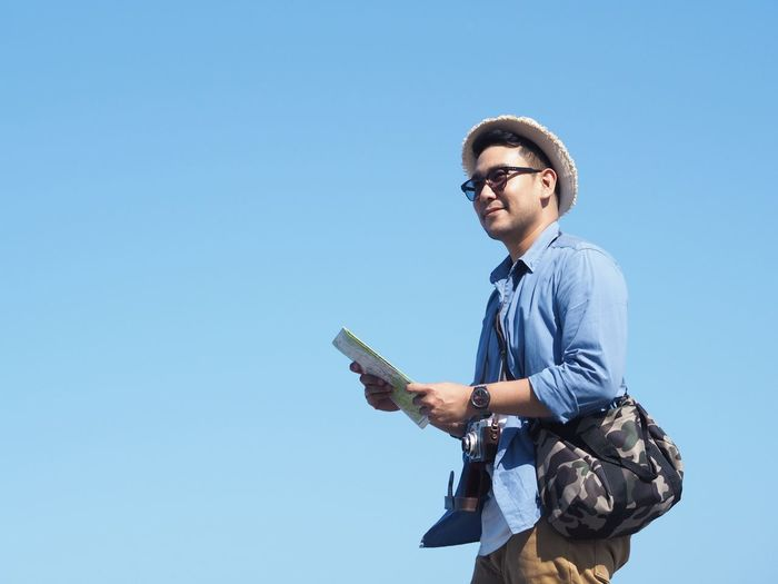 Low angle view of smiling man standing with map against clear blue sky