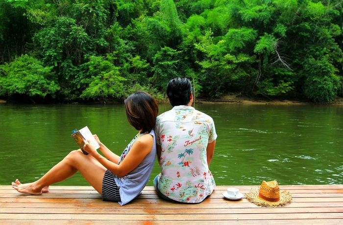 Lovely young couple in love relaxing enjoying river view and forest sitting and reading book together on the wooden floor with cup of coffee and straw hat. Romane and chill out in the morning. Boyfriend && Girlfriend ♡♥ Happiness Love Vacations Adults Only Beauty In Nature Couple - Relationship Duet Husband And Wife Lake Leisure Activity Nature Real People Relaxation Sitting Straw Hat Togetherness Travel Destinations Tree Two People Vacations Water Women Young Adult EyeEmNewHere