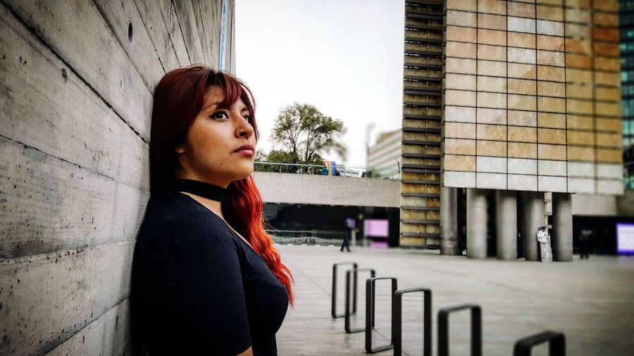 Side view of thoughtful young woman looking away while leaning on wall in city