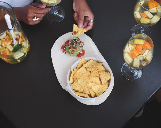 Cropped Hands Of Woman Eating Nachos On Table In Restaurant