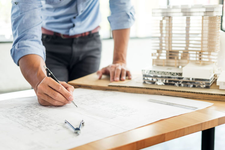 Midsection of architect working at table