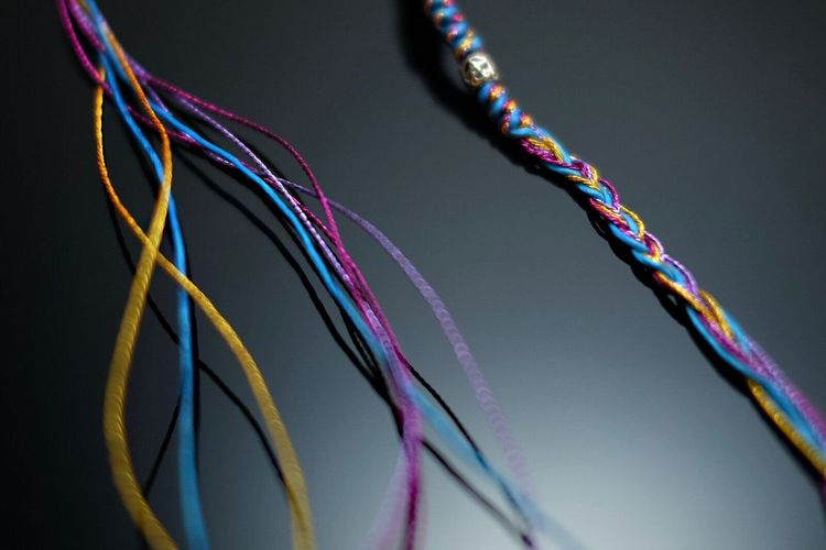 Close-Up Of Colorful Threads Against Gray Background