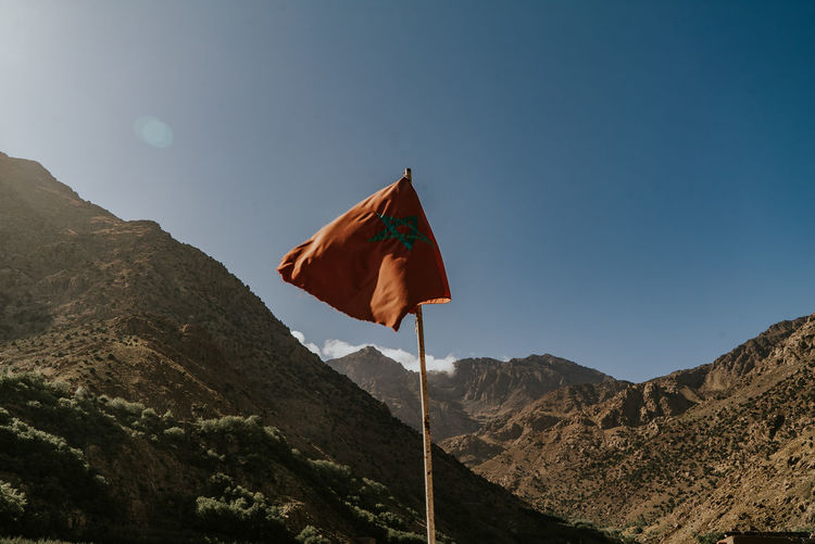 Low angle view of flag against mountain range