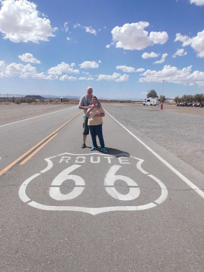 Full length of couple standing by road sign against sky