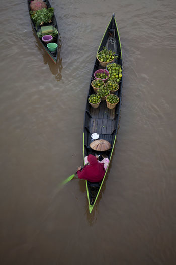 High angle view of woman with fruits traveling in boat on river